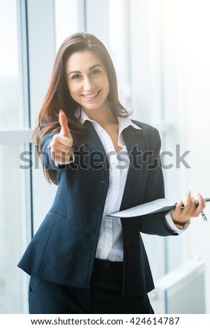 Young businesswoman sitting at workplace and reading paper in office with good, well sign by hands - stock photo