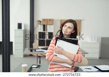 Young businesswoman sitting daydreaming with a smile on her face staring off to the side and clutching two office binders - stock photo