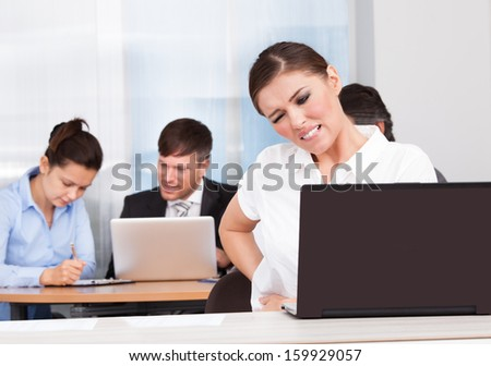 Young Businesswoman Sitting In Front Of Her Colleagues Suffering From Back Pain - stock photo
