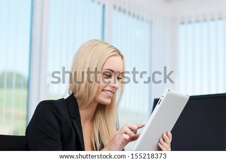 Young businesswoman sitting in her office working on a tablet computer navigating with her finger on the touchscreen - stock photo