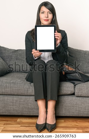 Young Businesswoman Sitting on a Gray Couch Showing an Empty Tablet Computer Screen, Emphasizing Copy Space. - stock photo