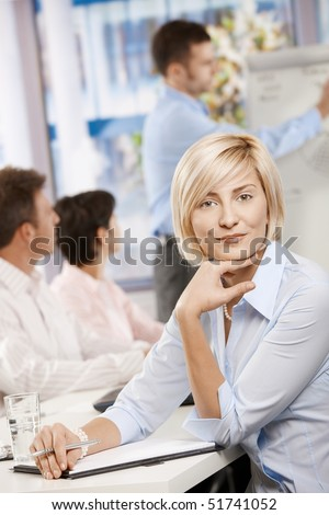 Young businesswoman sitting on business meeting in office making notes, looking at camera smiling. - stock photo