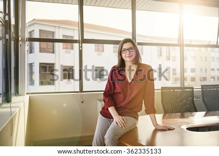 Young businesswoman sitting on the edge of a boardroom table with an expression of relaxed positivity and soft sunflare filtering through the large windows behind her - stock photo