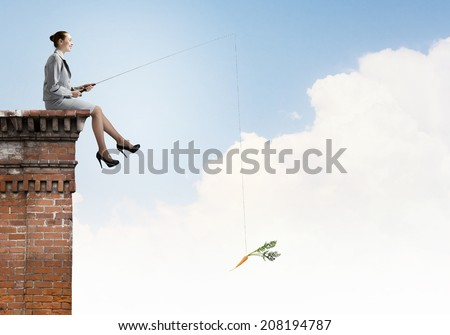 Young businesswoman sitting on top of building and fishing - stock photo