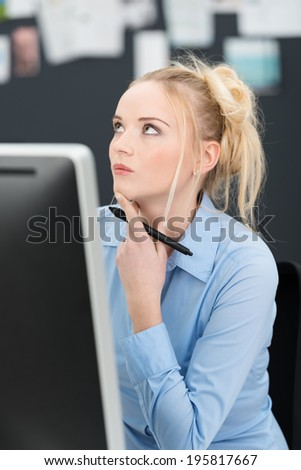 Young businesswoman sitting thinking at her desk with her hand holding a pen to her chin and her eyes raised in contemplation - stock photo