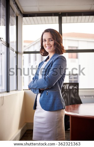 Young businesswoman smiling and standing with her arms crossed confidently in her office with large windows and buildings in the background where she runs her entrepreneurial business from - stock photo
