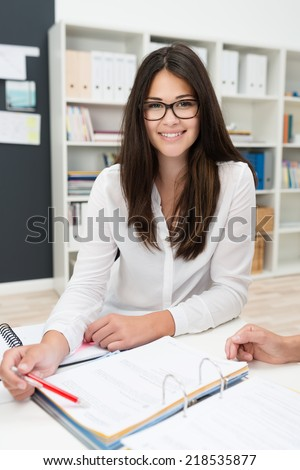 Young businesswoman smiling at the camera as she sits at her desk working on a file in the office - stock photo