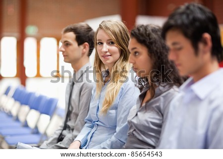 Young businesswoman smiling at the camera during a presentation - stock photo