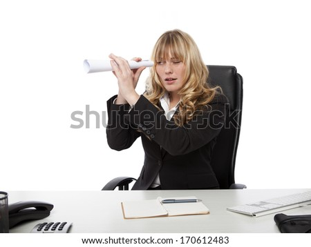 Young businesswoman spying on a colleague playfully holding a rolled up sheet of paper as a telescope to her eye - stock photo