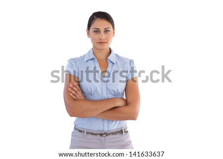 Young businesswoman standing alone with her arms crossed on white background - stock photo