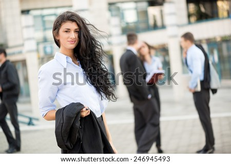 Young businesswoman standing in front of office building separated from the rest of the business team. With a smile looking at the camera. - stock photo