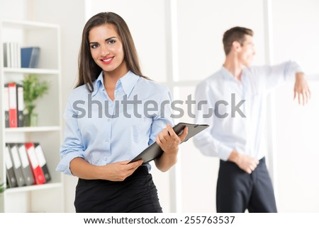 Young businesswoman standing in office with folder in hand, with a smile looking at the camera behind it is seen young businessman looking through the window of the office. - stock photo