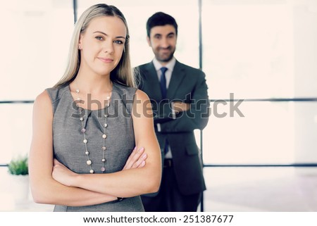 Young businesswoman standing in office with her collegue on the background - stock photo