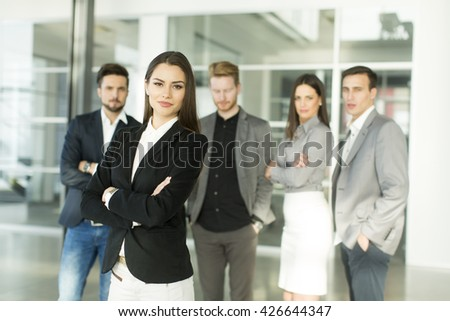 Young businesswoman standing in the office and other young business  people posing in the background - stock photo