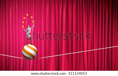 Young businesswoman standing on ball juggling with balls - stock photo