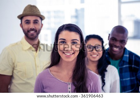 Young businesswoman standing with team in creative office - stock photo