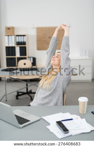 Young businesswoman stretching at her desk in the office with a smile of pleasure as she finishes her work - stock photo