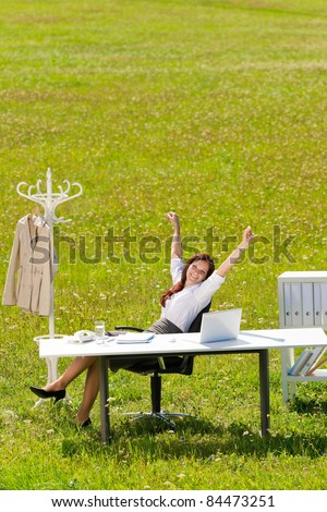 Young businesswoman stretching behind table in sunny meadow nature office - stock photo