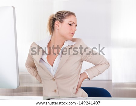 Young Businesswoman Suffering From Back Pain At Office - stock photo