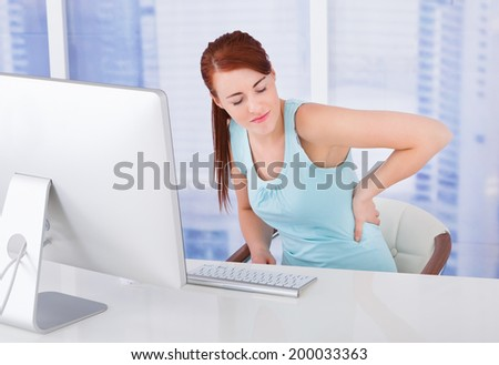 Young businesswoman suffering from backache at computer desk in office - stock photo