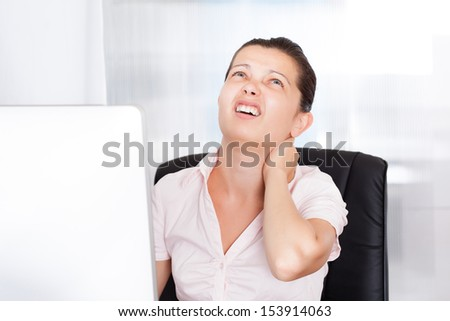 Young Businesswoman Suffering From Neck Pain In Front Of Computer - stock photo