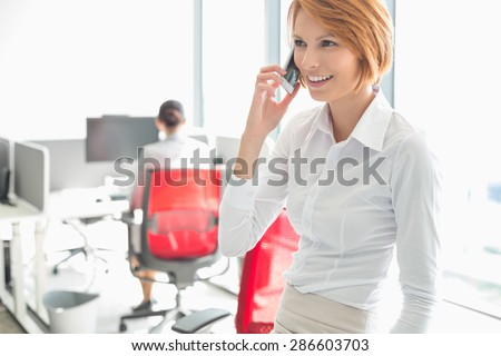 Young businesswoman talking on cell phone with colleagues in background at office - stock photo