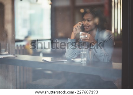 Young businesswoman talking on phone in coffee shop - stock photo