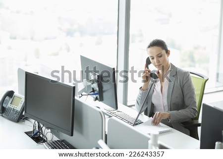 Young businesswoman talking on telephone in office - stock photo