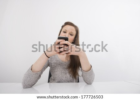 Young businesswoman text messaging on smart phone at office desk - stock photo