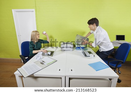 Young businesswoman throwing paper ball at male colleague holding waste bin - stock photo