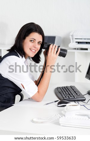 young businesswoman using binoculars in office - stock photo