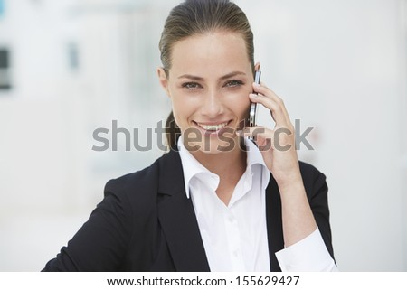 Young businesswoman using cellphone, smiling - stock photo