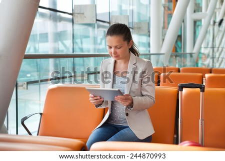 Young businesswoman using digital tablet while waiting for flight at airport lobby - stock photo