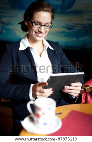 Young businesswoman using her tablet computer on a coffee break. Selective focus - stock photo
