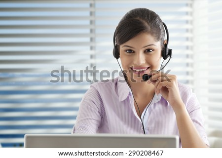 Young businesswoman using laptop in office , wearing headset - stock photo
