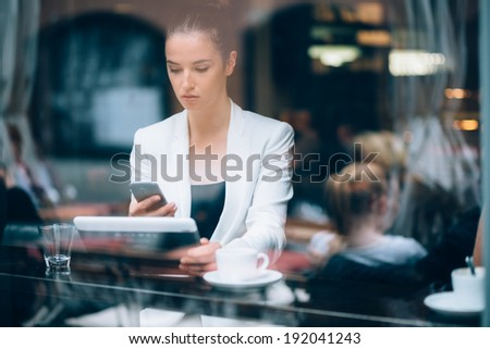 Young businesswoman using phone and tablet computer in coffee shop - stock photo