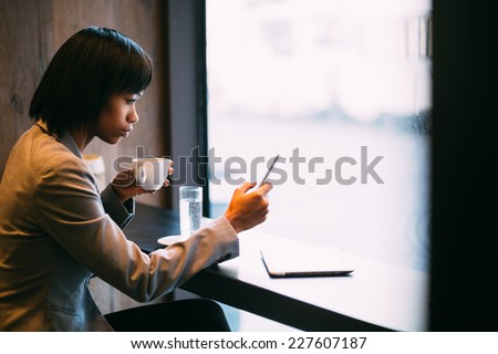 Young businesswoman using phone in coffee shop - stock photo