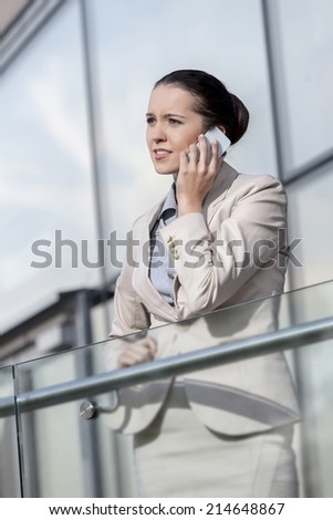 Young businesswoman using smart phone at office railing - stock photo