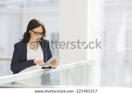 Young businesswoman using tablet PC in office - stock photo