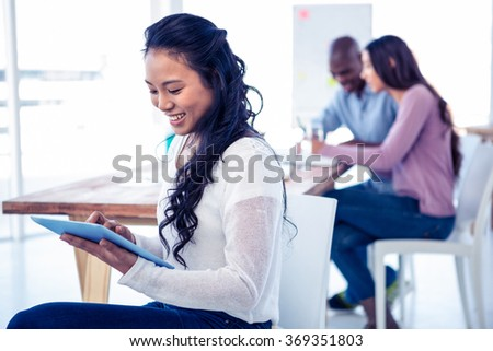 Young businesswoman using tablet PC with colleagues in background at creative office - stock photo