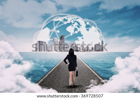 Young businesswoman walking on the highway toward the cityscape - stock photo