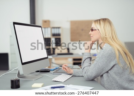Young businesswoman wearing glasses sitting at her desk reading her blank white computer screen, profile view in the office - stock photo