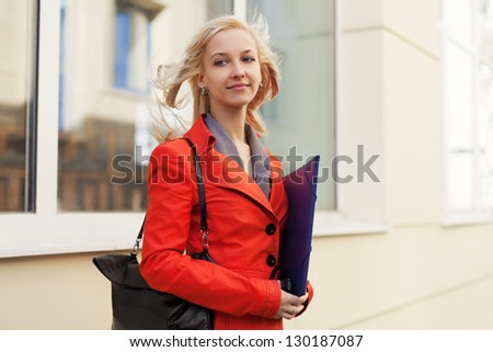 Young businesswoman with a folder against office windows - stock photo