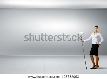 Young businesswoman with a paint brush against white wall - stock photo