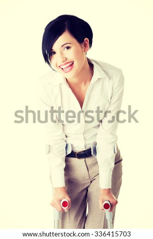Young businesswoman with crutches. Disabled person in work. - stock photo
