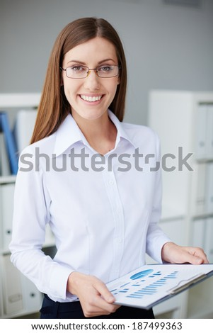 Young businesswoman with document looking at camera in office - stock photo