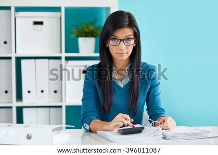 Young businesswoman with glasses calculates tax at desk in office - stock photo