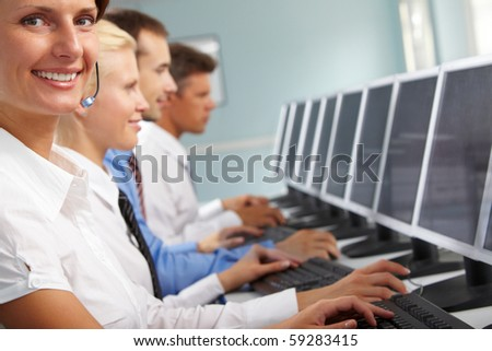 Young businesswoman with headset looking at camera in working environment - stock photo