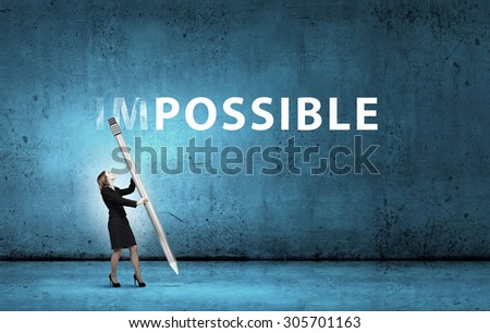 Young businesswoman with huge pencil changing word impossible - stock photo