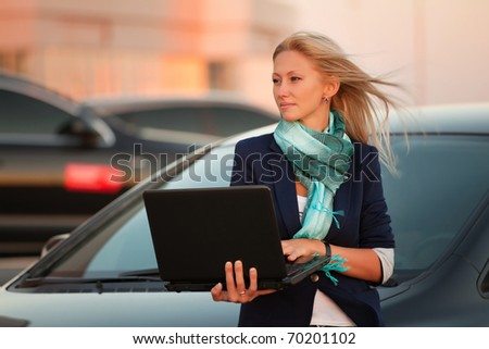 Young businesswoman with laptop on the car parking - stock photo